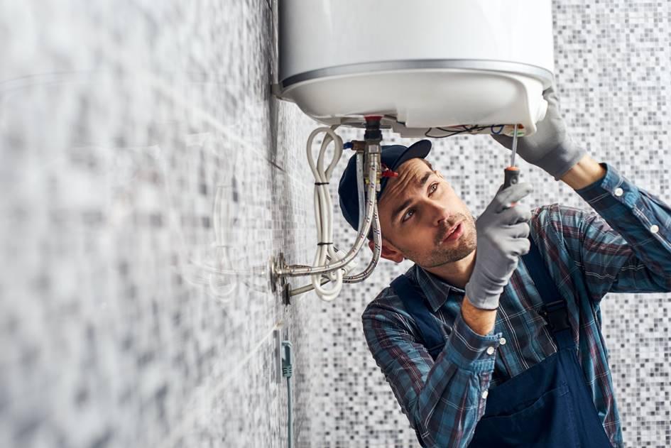 Installateur bei der Reaparatur eines Boilers in einem privaten Badezimmer